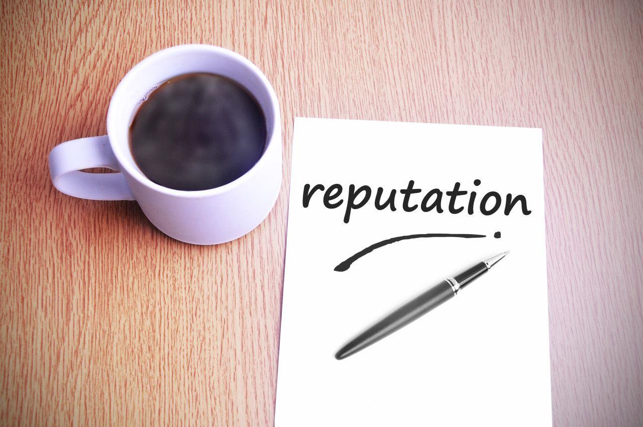 biely papier s nápisom reputation na ktorom je položené čierne pero a vedľa horúca káva v bielej šálke