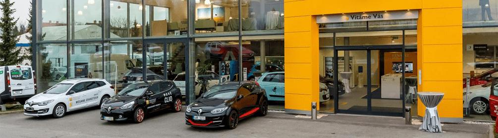 čierne a biele autá pred predajňou oranžová vstupná brana renault